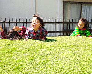 人工芝を張り終えて喜ぶ子供達。
